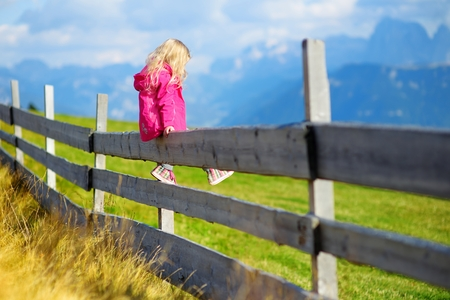 Cute little girl sitting on wooden fence admiring beautiful landscape in Dolomites mountain range, South Tyrol province of Italy Stock Photo
