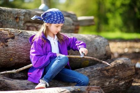 Schattig klein meisje zittend op een boom logboeken met behulp van een zakmes aan whittle een wandel-stick. Kind met een vleesmes.