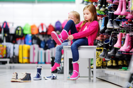 Two little sisters choosing and trying on new rain boots in a store Stock Photo