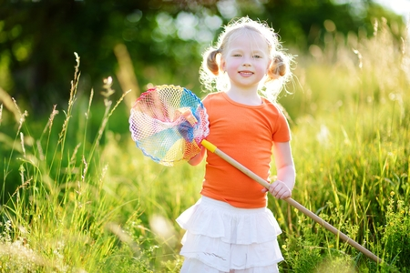 peacefull: Cute little girl catching butterflies and bugs with her scoop-net on beautiful sunny summer day