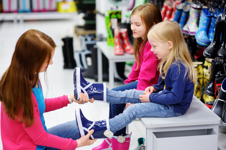 Young mother and her two little girls choosing and trying on new rain boots in a store