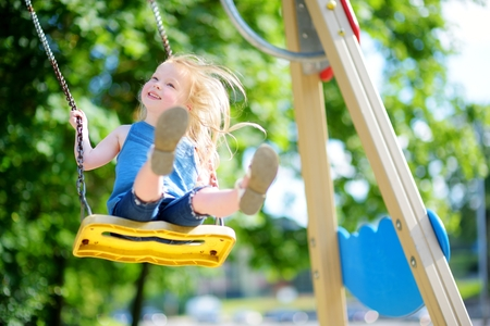 Cute little girl having fun on a playground outdoors in summer Stock Photo