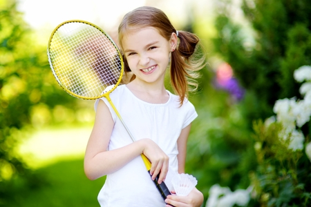 shuttlecock: Cute little girl playing badminton outdoors on warm and sunny summer day