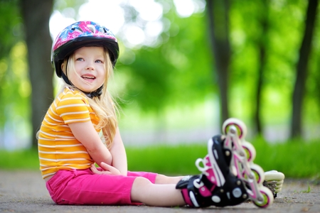 skate park: Pretty little girl learning to roller skate outdoors on beautiful summer day