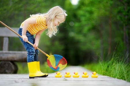 Funny little girl helping five rubber ducklings to cross the street