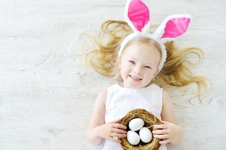 Nettes kleines Mädchen mit Hasenohren eijagd auf Ostern zu spielen. Entzückendes Kind, Ostern zu Hause zu feiern. Standard-Bild - 70292565
