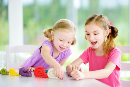 Twee leuke kleine zusters plezier samen met kleurrijke boetseerklei op een kinderdagverblijf. Creatieve kinderen vormen thuis. Kinderen spelen met plasticine of deeg.