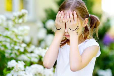 Cute little girl covering her face with her hands on summer day. Sad child with eyes pictured on her palms.