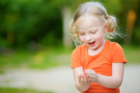 Adorable little girl catching little babyfrogs on beautiful summer day in forest