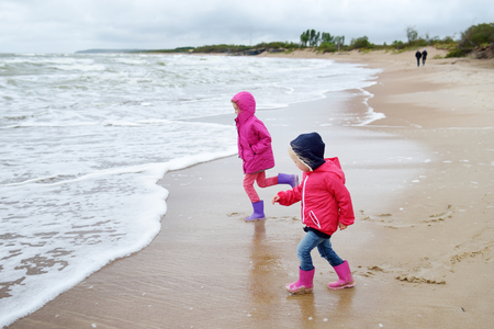 Two little sisters having fun on a sandy beach of Baltic sea at summertime