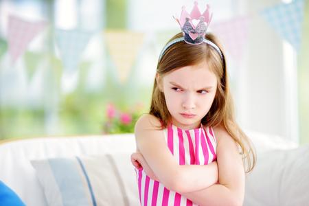 Moody niña llevaba tiara princesa enojado e insatisfecho. Concepto de berrinche de los niños.