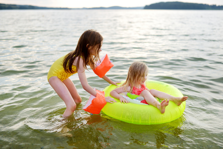 Little sisters having fun swimming in a lake using inflatable rubber ring on warm summer evening Stock Photo