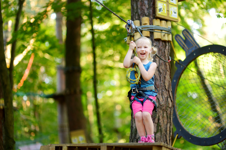 clambering: Adorable little girl enjoying her time in climbing adventure park on warm and sunny summer day. Summer activities for young kids. Child having fun on school vacations.