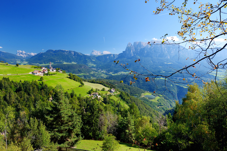 Scenic view of small Alpine village located in South Tyrol, RenonRitten region, Italy. Beautiful rocky mountain range on a background.