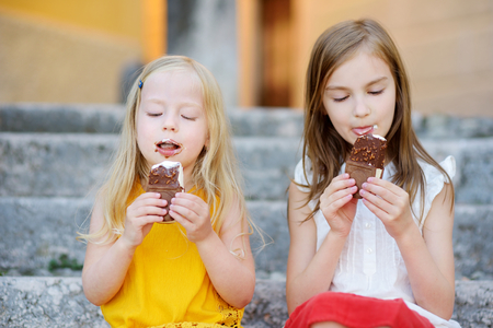 Two cute little sisters eating ice-cream while sitting on the stairs on bright summer day Banco de Imagens - 70964401