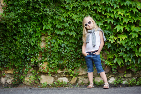 Funny little girl wearing sunglasses posing by bindweed wall on warm and sunny summer day in italian town