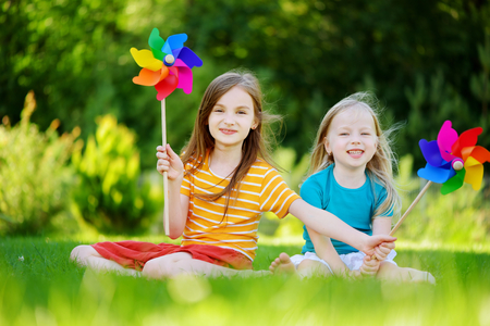 pinwheels: Two cute little girls holding colorful toy pinwheels on warm and sunny summer day