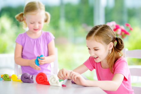 Two cute little sisters having fun together with colorful modeling clay at a daycare. Creative kids molding at home. Children play with plasticine or dough.