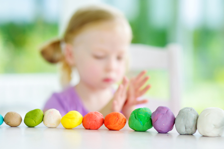 Cute little girl having fun with colorful modeling clay at a daycare. Creative kid molding at home. Child play with plasticine or dough.