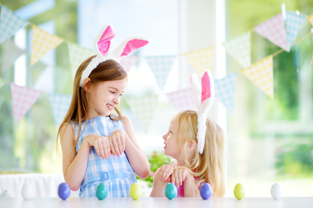 Two cute little sisters wearing bunny ears playing egg hunt on Easter. Adorable children celebrate Easter at home.