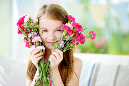 many babies: Adorable smiling little girl holding flowers for her mom on mothers day