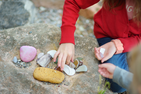 Two cute little sisters collecting beautiful stones on a pebble beach on summer day Stock Photo