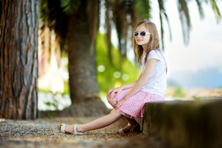 maderno: Cute little girl wearing sunglasses on a shore of lake Garda in Toscolano-Maderno, a small town and comune in the province of Brescia, in Lombardy, Italy Stock Photo