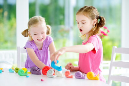 modeling clay: Two cute little sisters having fun together with colorful modeling clay at a daycare. Creative kids molding at home. Children play with plasticine or dough.