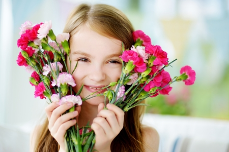 Adorable smiling little girl holding flowers for her mom on mother's day