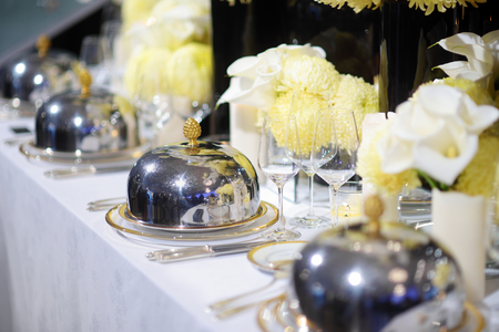 formal dinner party: Beautiful table setting with crockery and flowers for a party, wedding reception or other festive event. Glassware and cutlery for catered event dinner.