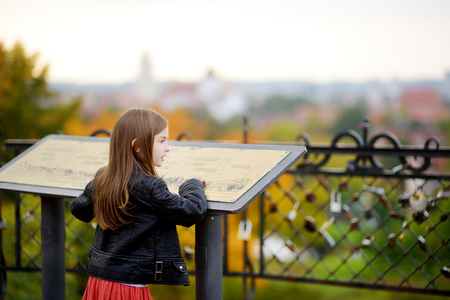 Cute little girl enjoying a view of Vilnius city on autumn day. Child examining information board.