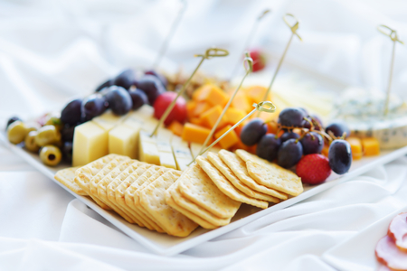 baguet: Different kinds of wine snacks: cheeses, baguettes, crackers, fruits and olives on white table