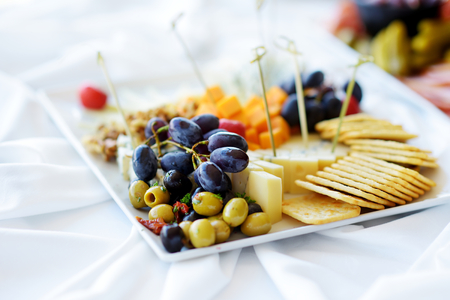 Different kinds of wine snacks: cheeses, baguettes, crackers, fruits and olives on white table