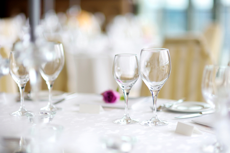 Beautiful table setting with crockery and flowers for a party, wedding reception or other festive event. Glassware and cutlery for catered event dinner.