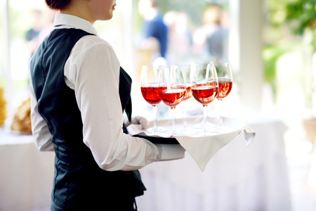 Waitress holding a dish of champagne and wine glasses at festive event, party or wedding reception