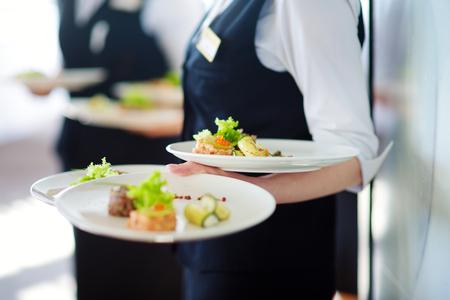 Cameriere che porta piatti con piatto di carne su qualche evento festivo, festa o ricevimento di nozze Archivio Fotografico - 73220250