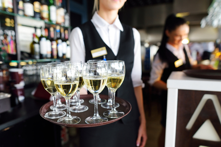 skoal: Waitress holding a dish of champagne and wine glasses at festive event, party or wedding reception