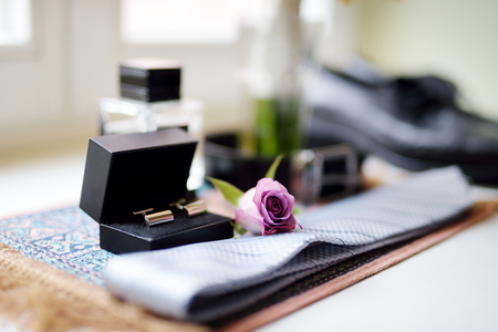 Grooms wedding accessories: tie, belt, shoes and two golden cuff links in black box