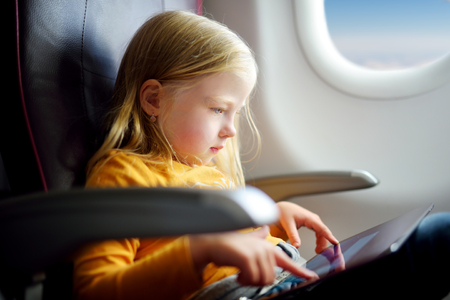 adentro y afuera: Adorable little girl traveling by an airplane. Child sitting by aircraft window and using a digital tablet during the flight.