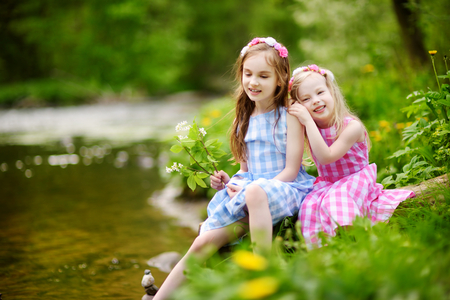 Two adorable little sisters playing by a river in sunny park on a beautiful summer day. Children enjoying their time together. Stock Photo