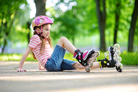 skate park: Pretty little girl learning to roller skate on beautiful summer day in a park. Child wearing safety helmet enjoying roller skating ride outdoors. Stock Photo