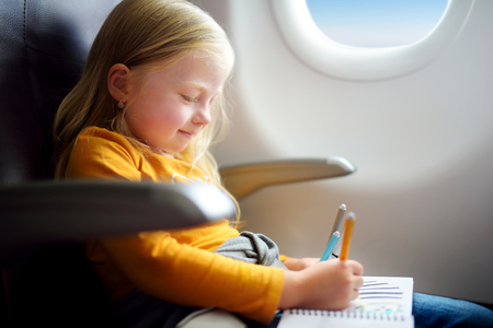adentro y afuera: Adorable little girl traveling by an airplane. Child sitting by aircraft window and drawing a picture with colorful felt-tip pens.
