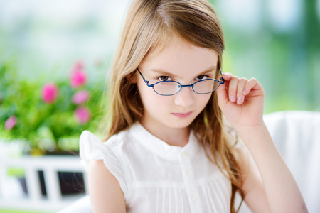 expressive: Portrait of beautiful little girl wearing glasses at home. Vision, health, ophthalmology concept.