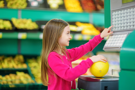 Cute little girl shopping in a food store or a supermarket