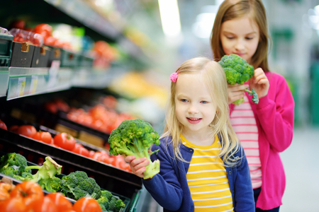 Two cute little sisters choosing fresh broccoli in a food store or a supermarket Stock Photo