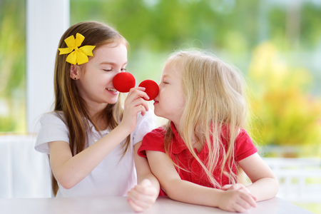 Happy little sisters wearing red clown noses having fun together on sunny summer day at home. Two kid playing together. Stock Photo