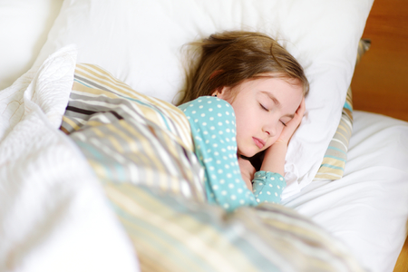 taking nap: Adorable little girl sleeping in the bed. Tired child taking a nap under white blanket. Bedtime for kids. Stock Photo
