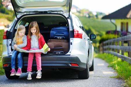 Twee schattige kleine meisjes klaar om te gaan op vakantie met hun ouders. Kinderen zitten in een auto de behandeling van een kaart. Reizen met de auto met kinderen.