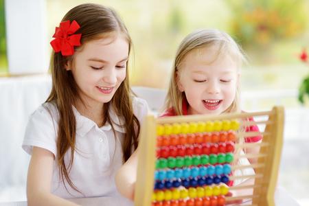 Twee leuke meisjes die met telraam thuis spelen. Grote zus leert haar broer of zus om te tellen. Slim kind leren tellen. Kleuter met plezier met educatief speelgoed thuis of op de kleuterschool.
