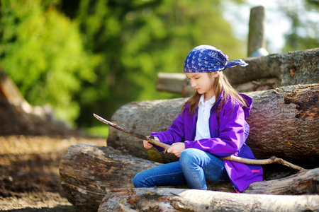 whittle: Cute little girl sitting on tree logs using a pocket knife to whittle a hiking stick. Child using a carving knife. Stock Photo